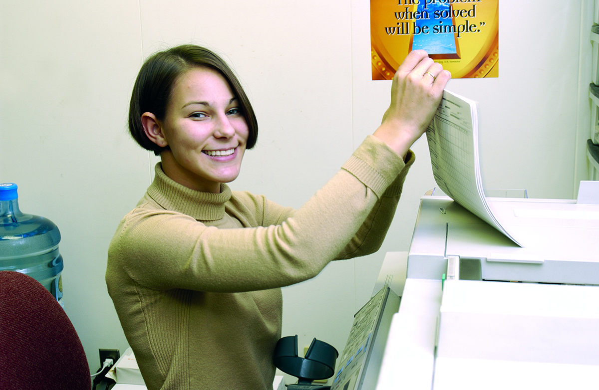 oung woman smiling toward viewer as she uses a copy machine at work.