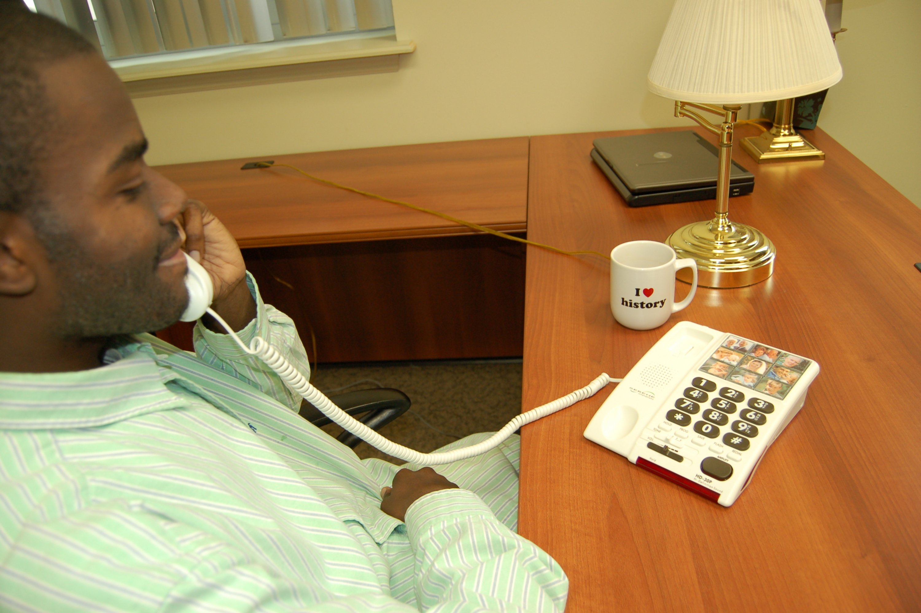 oung man at an office desk talking on a phone which feature large buttons and picture but