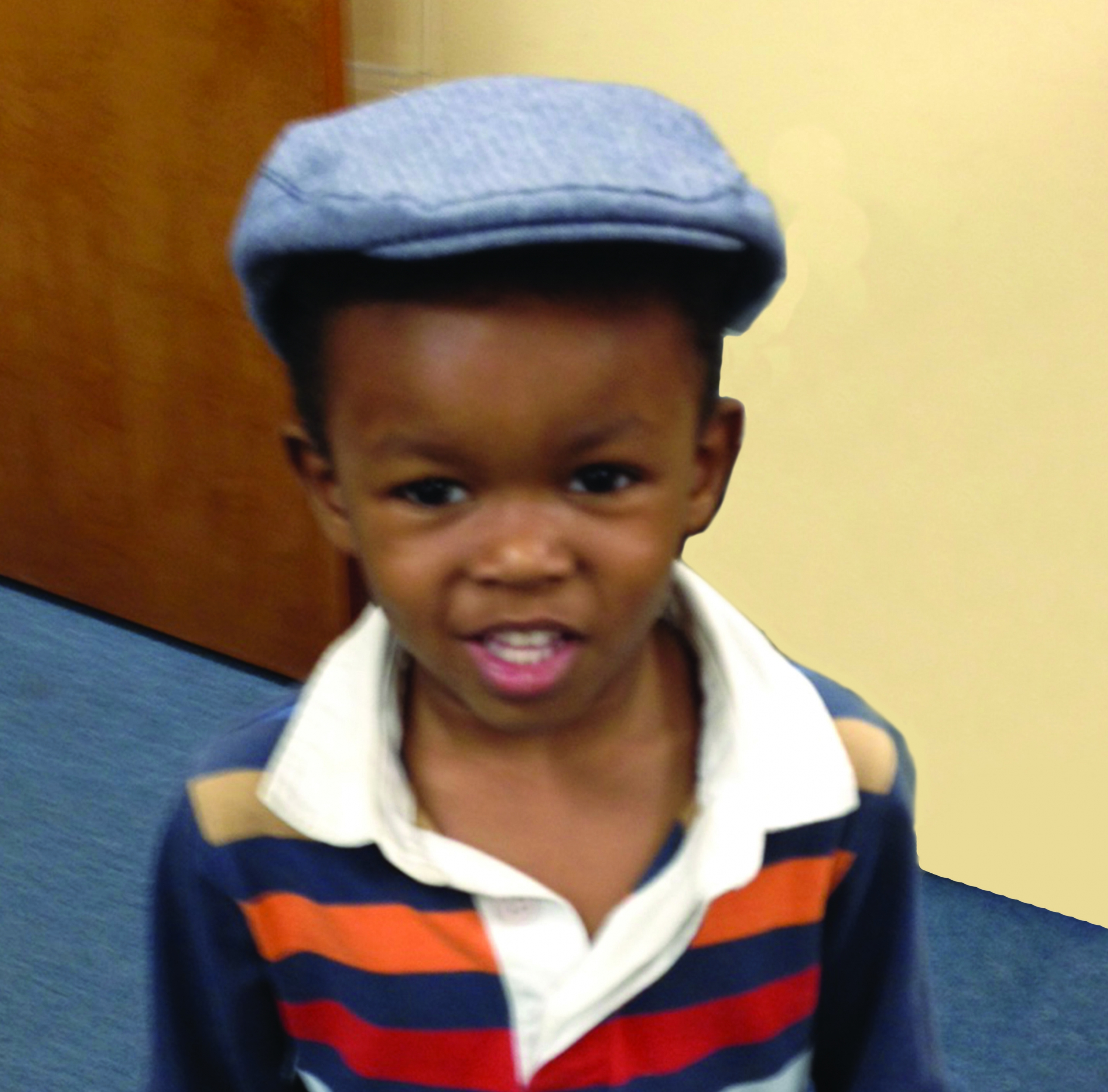 smiling toddler boy (dressed in cap and striped shirt)